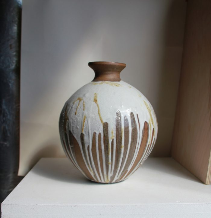 An elegant pot, with a brown rim, white base layer, and brown streaks drawn smoothly down the side.
