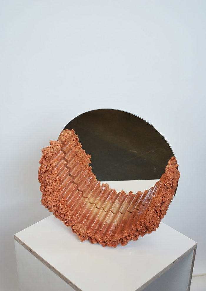 Circular mirror with coral-coloured foam creeping across the glass on one side.