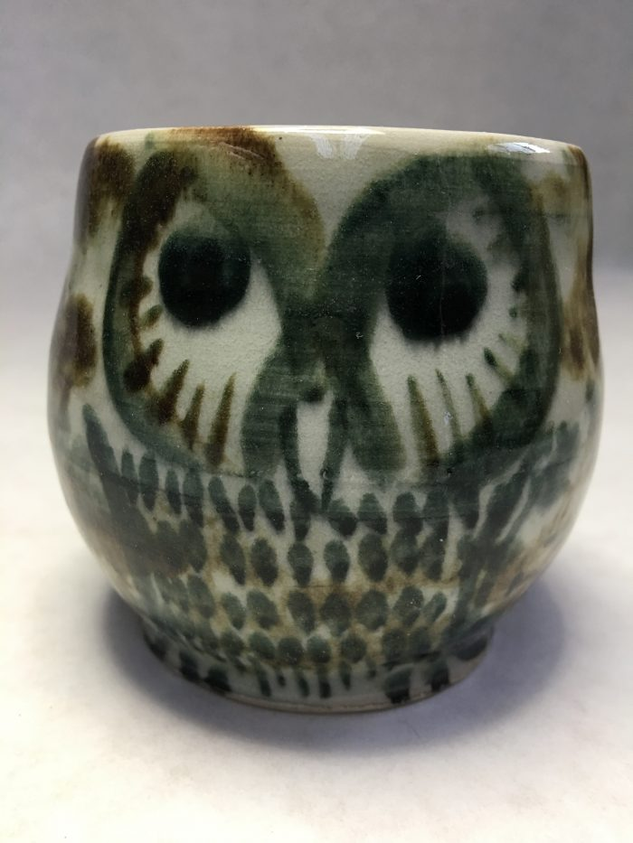 Cup with an owl painted on it. it's grey and brown.