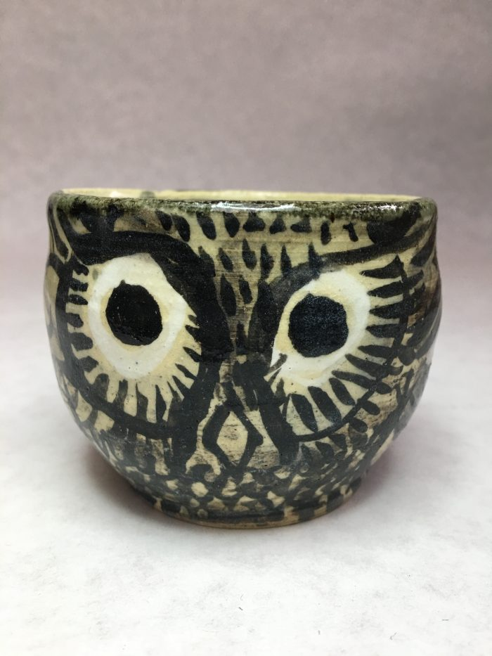Small cup with a grey owl with big eyes painted on the side.