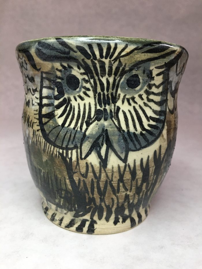 Stone cup with curving sides and a stately-looking grey and brown owl painted on it.
