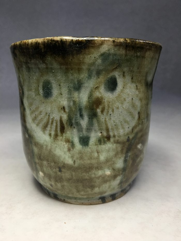 Brown owl painted on the side of a tall stone cup.