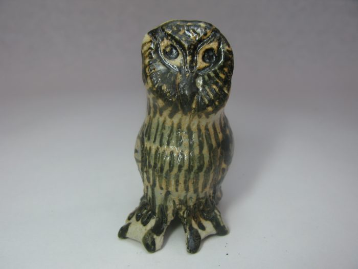 Stone model of a brown striped owl.