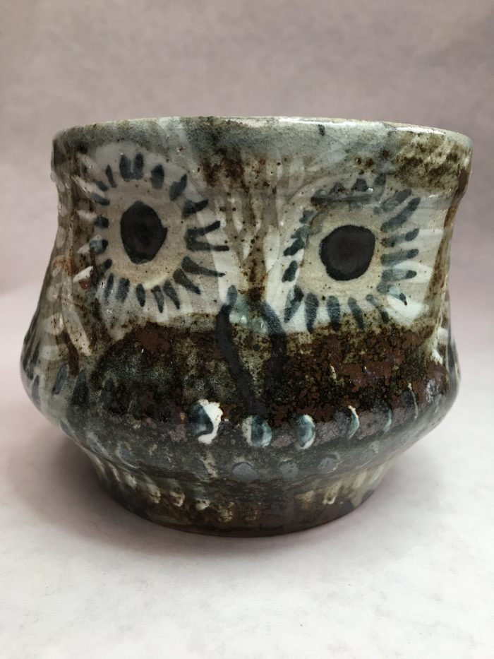 Stone cup with curving sides and a brown and white owl painted on it.