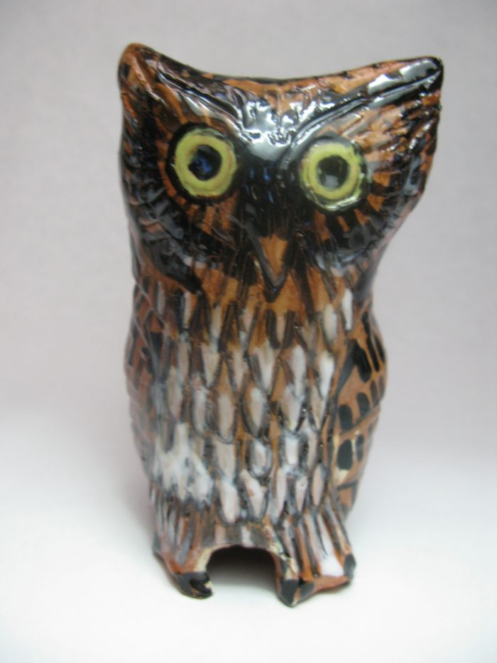 Orange brown owl figure with white stripes and large yellow eyes.