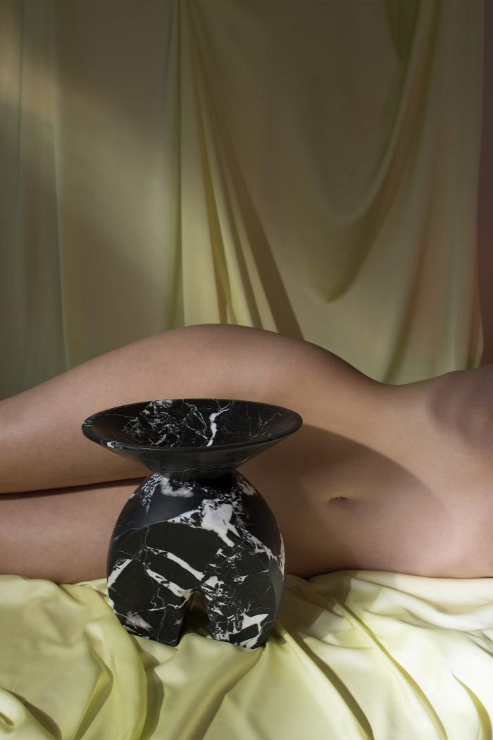 Black vase with white marbling. Sitting in front of a person lying down naked behind it.