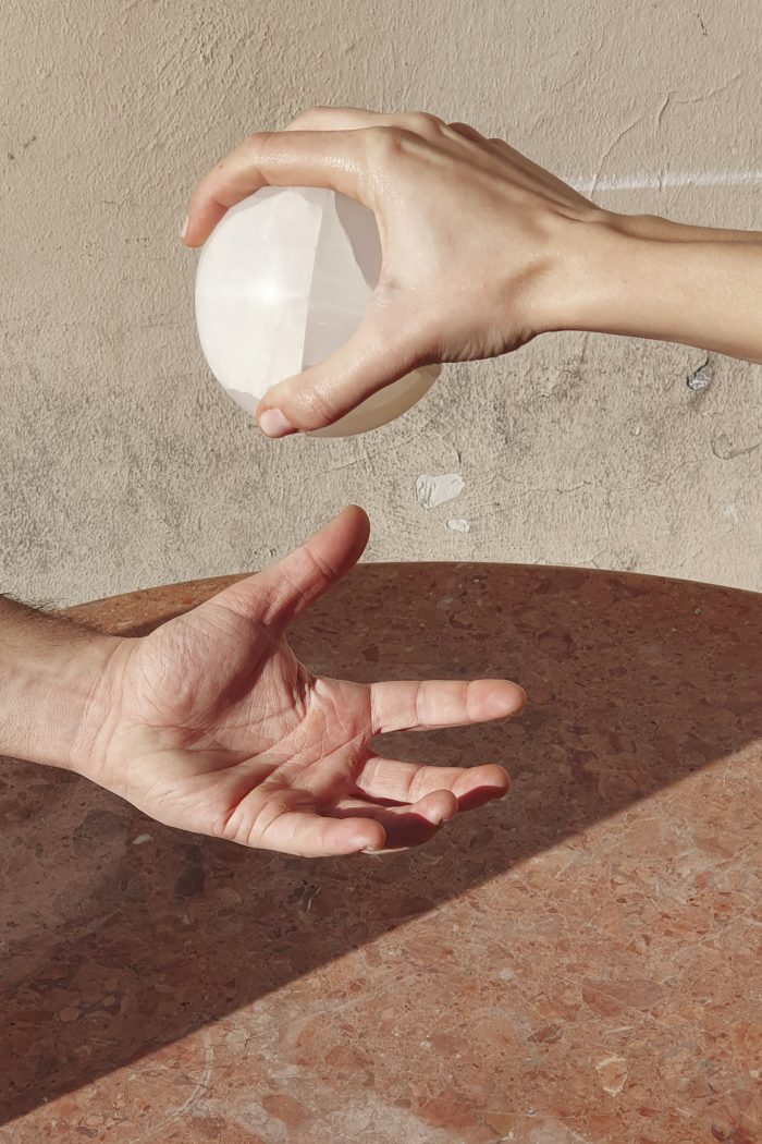 The spherical white eye container being handed from one hand to another.