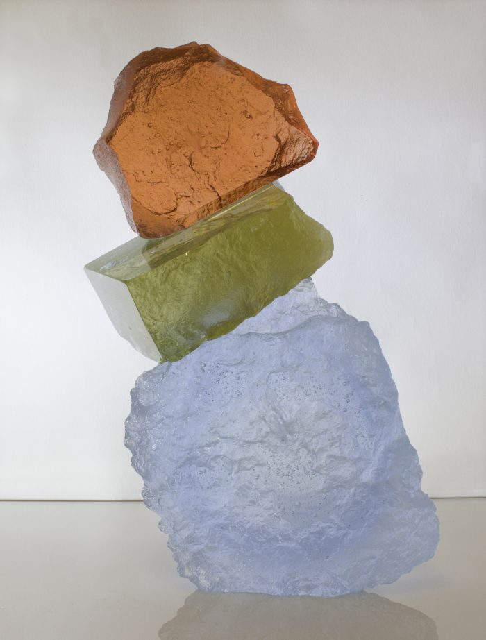 A glass sculpture appearing as if hewn from rock. A rough square cut white makes the base, and supports a rock-like piece of green glass which in turn supports a rough piece of rust orange glass. The entire piece leans in a natural way.
