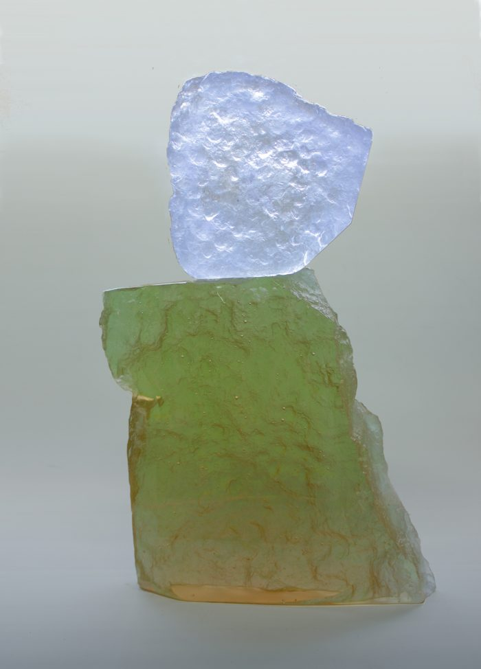 A glass sculpture which appears as if hewn from a rock-face. A tall, brownish yellow base is perched upon by a small, jagged square of white glass.