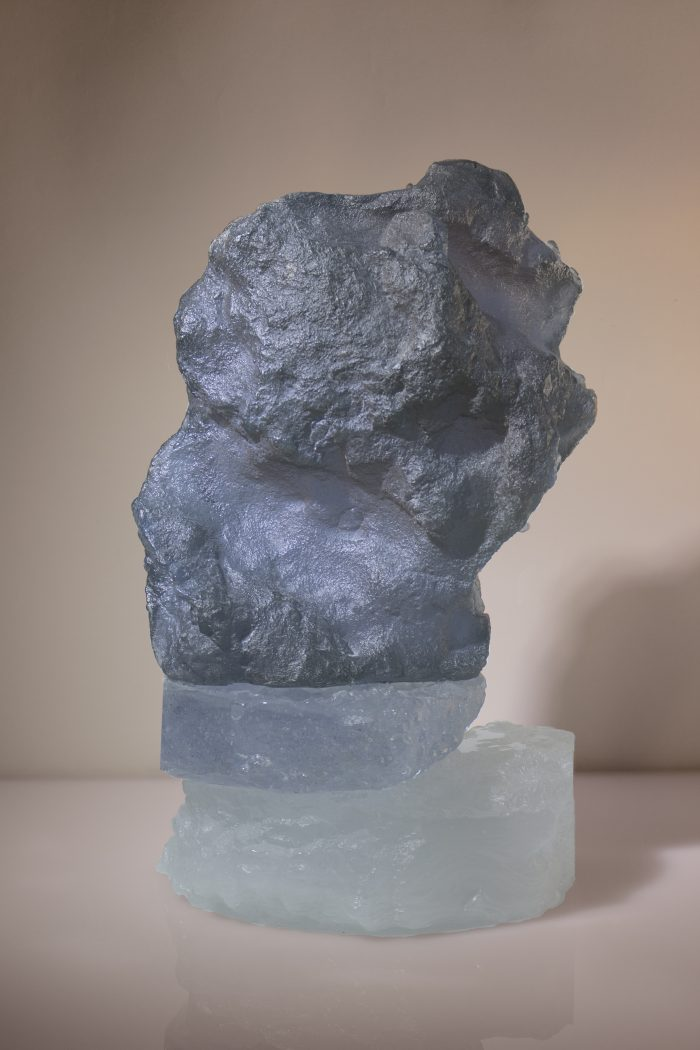 Rock-like sculpture formed grom grey and semi-opaque white glass. A captivating form stretching to the sky, placed on the edge of the base in a natural way.