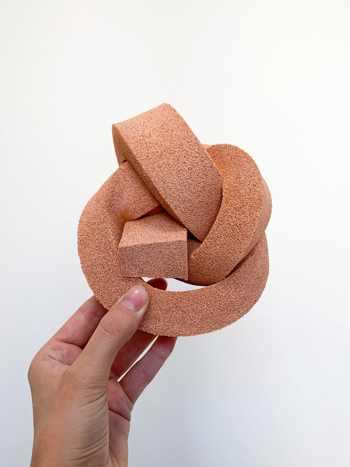 A terracotta-coloured knot made from foam.
