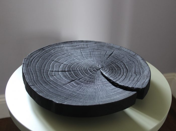 Flat, elegant black wood platter, reminiscent of the top of a tree stump - all natural wood lines and curves.