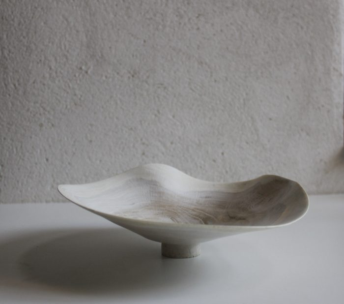 A soft white wood bowl, with a waving rim, on a narrow foot.