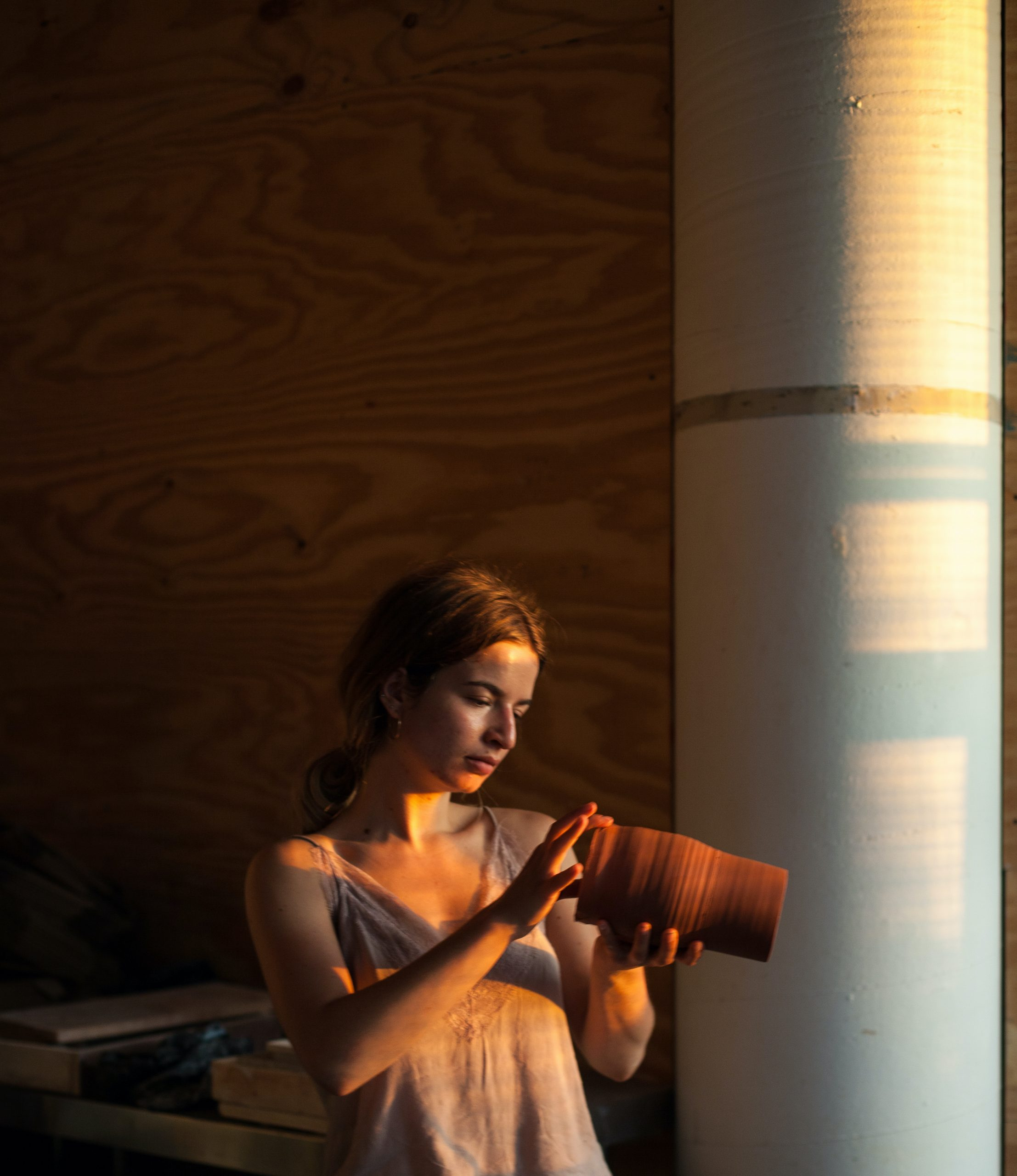 Artist Karina Smagulova is expertly handling a pot in a studio bathed in soft evening sunlight.
