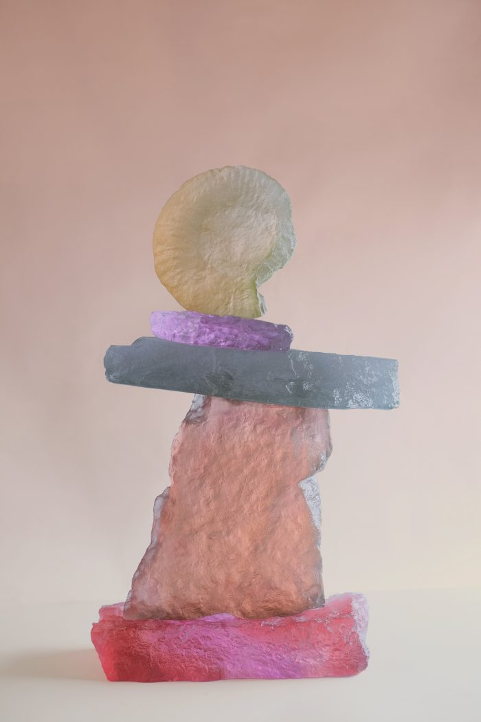 A delicately balanced glass sculpture of 5 pieces perched upon each other. They form a narrow tower of interchanging flat wide pieces and tall narrow pieces of colours ranging from pink, to blue, to purple to yellow. At the top is impossibly balanced a large glass yellow seashell.