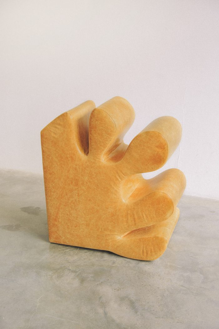 A piece of furniture designed like an abstract image of a yellow hand. Here it is placed upright on it's side to be leaned back onto.