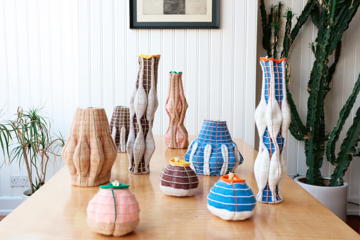 A collection of textile vessels of various heights and shapes placed along a table, made in bright colours from blue, to deep purple to white and brown.