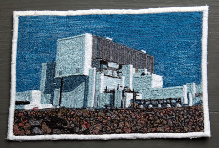 Detailed embroidered patch, in muted blue, white and brown, depicting a building on a stone beach against a blue sky.