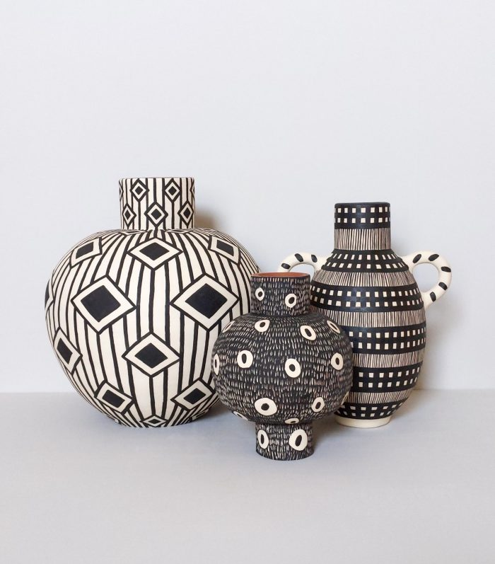 A collection of three pots decorated in loose geometric patterns.