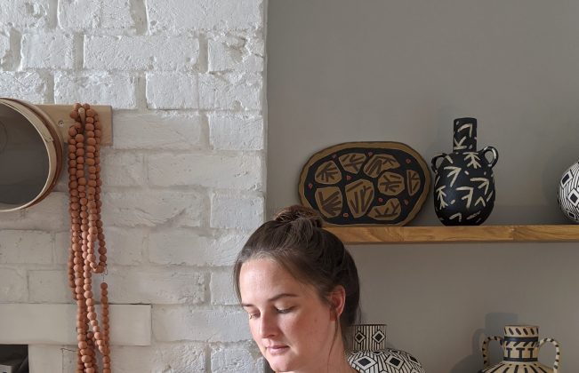 Artist Lydia Hardwick kitted out in her pottery apron and looking pensively at the ceramic she's holding, against a backdrop of white brick and her own pieces displayed on shelving.