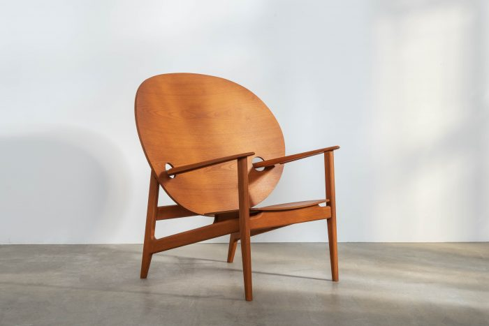 Large, light brown chair with a curving solid back.