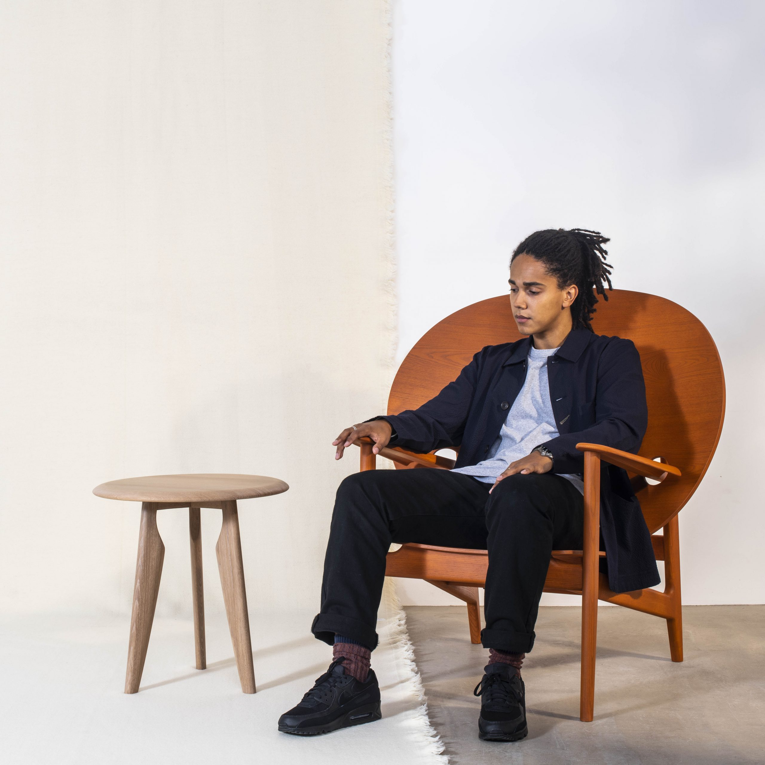Artist Mac Collins reclines in a circle backed orange chair besides a side table, looking relaxed and dressed in navy, black and blue.
