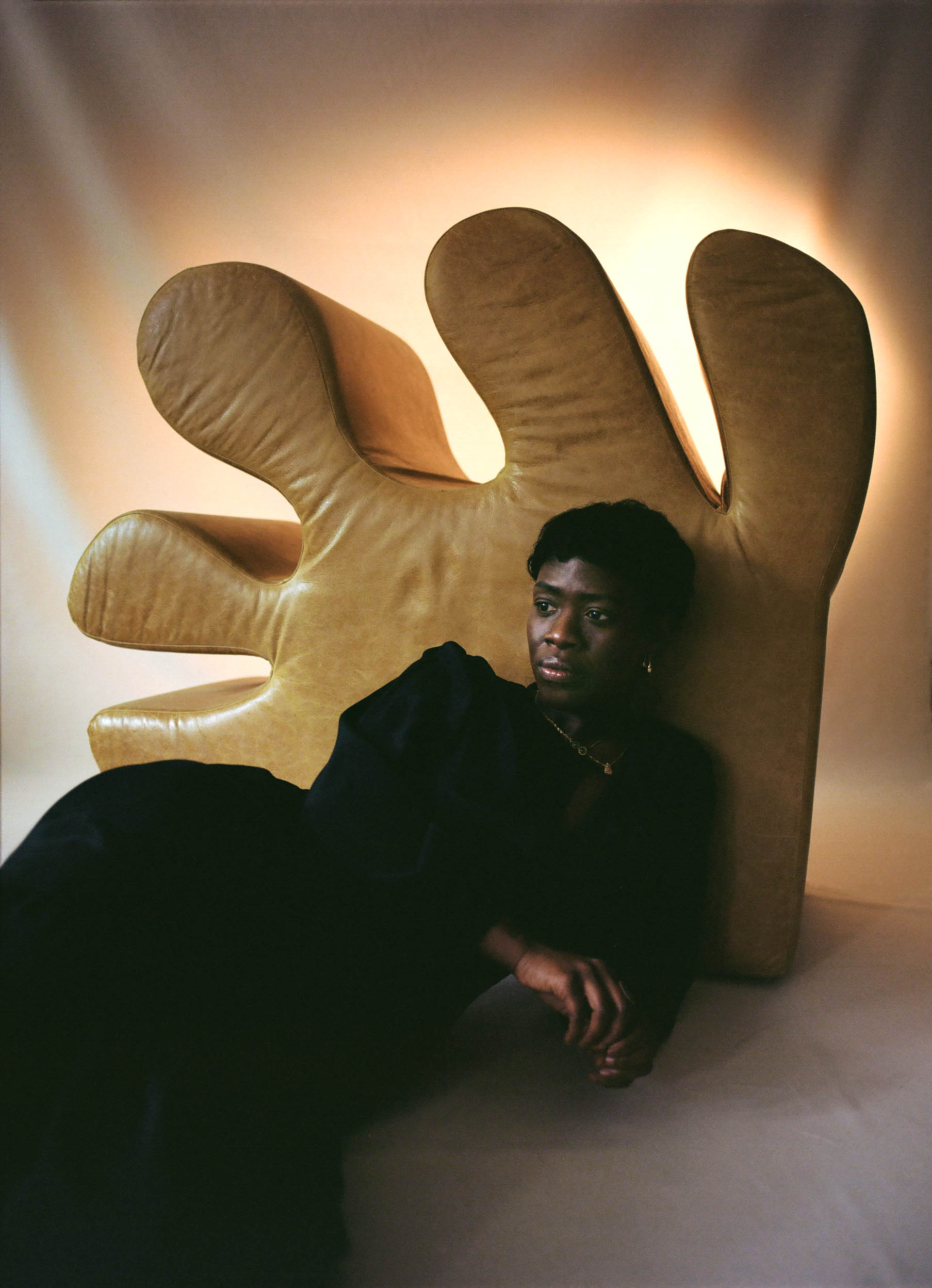 Artist Kusheda Mensah lying back into her furniture piece The Hand, back-lit and relaxed in a stylish black dress.