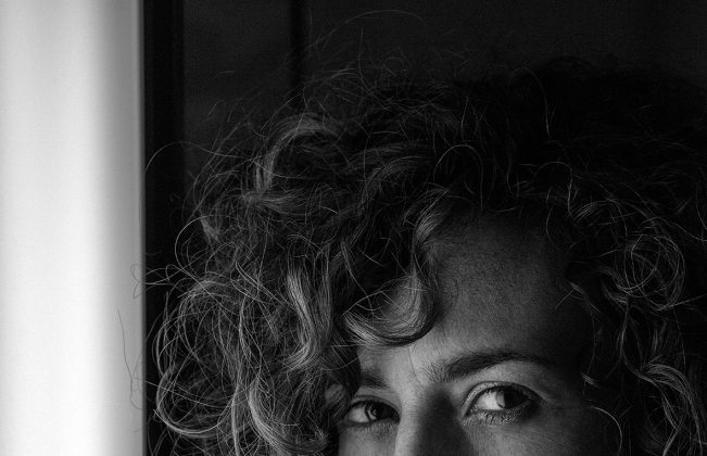 Artist Natascha Madeiski shown in black and white, leaning by a window and looking directly at the viewer.