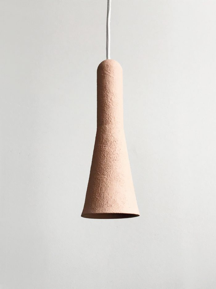Pale pink, textured light in an elegant narrow cone shape hanging down.