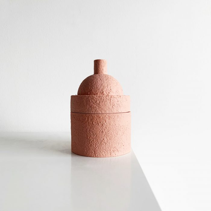 Small, pink, textured container with a rounded top and a point at its peak.