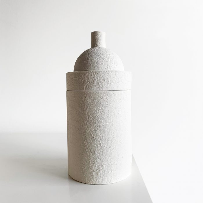 Textured tall white container, with a curved top.