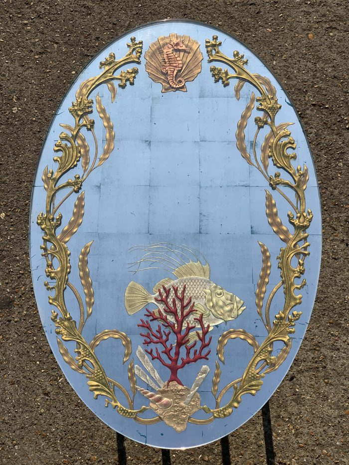 Oval mirror with gold seaweed running up its sides , and a gold fish behind a vivid red coral design at the bottom of the mirror.