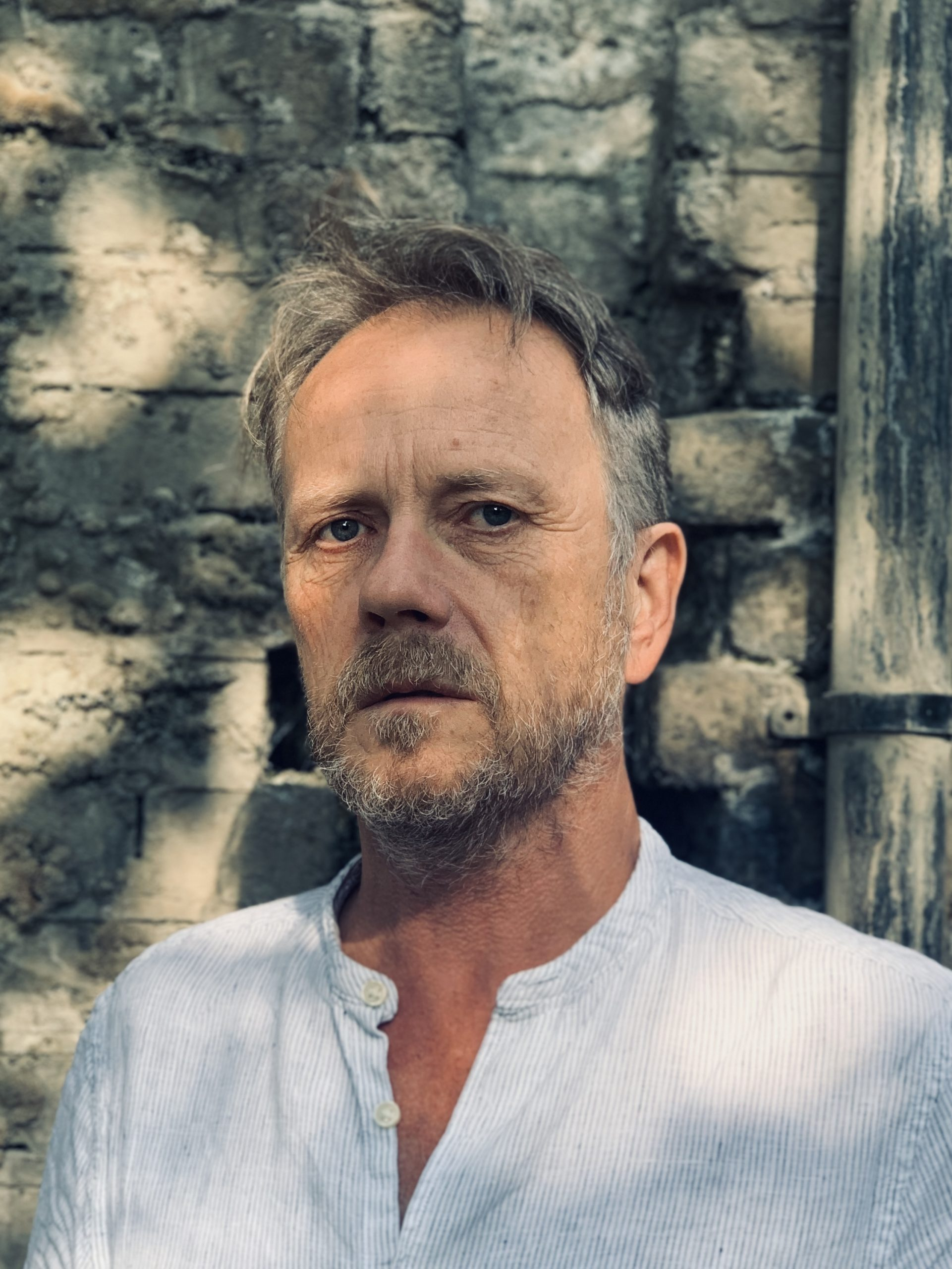 Standing against a grey brick wall in dappled light, artist Paul Clifford looks seriously into the camera, wearing a white shirt