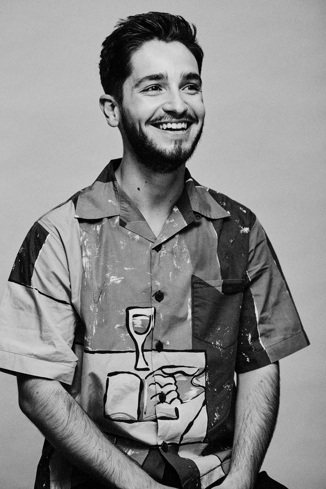 Artist Robson Stannard portrayed in black and white, wearing an eclectic patterned shirt and smiling off camera.
