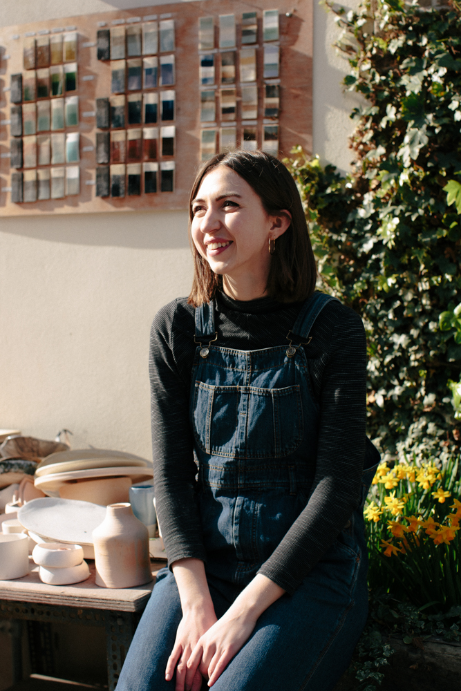 Artist Ania Brzeski of Sloth sits in denim overalls over a black jumper in her studio, bathed in sunlight and smiling.