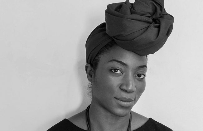 Artist Simone Brewster, shown in black and white, leans against a wall in a simple black outfit and large necklace and looks at the camera knowingly.