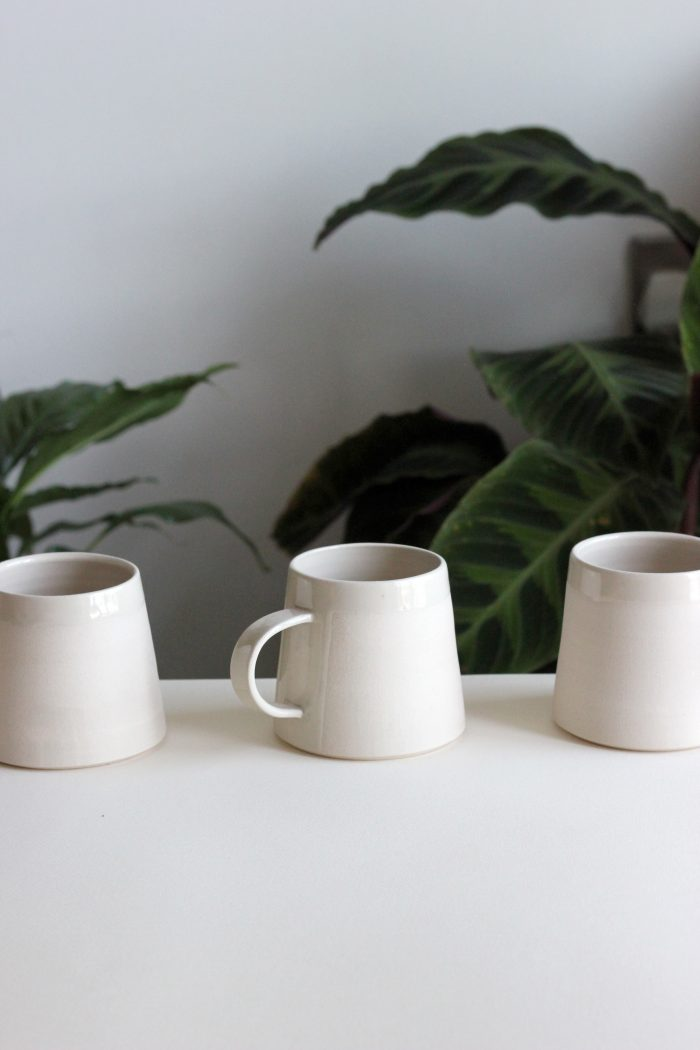 Mug with a wide base and a slightly tapered rim, in white with a handle.