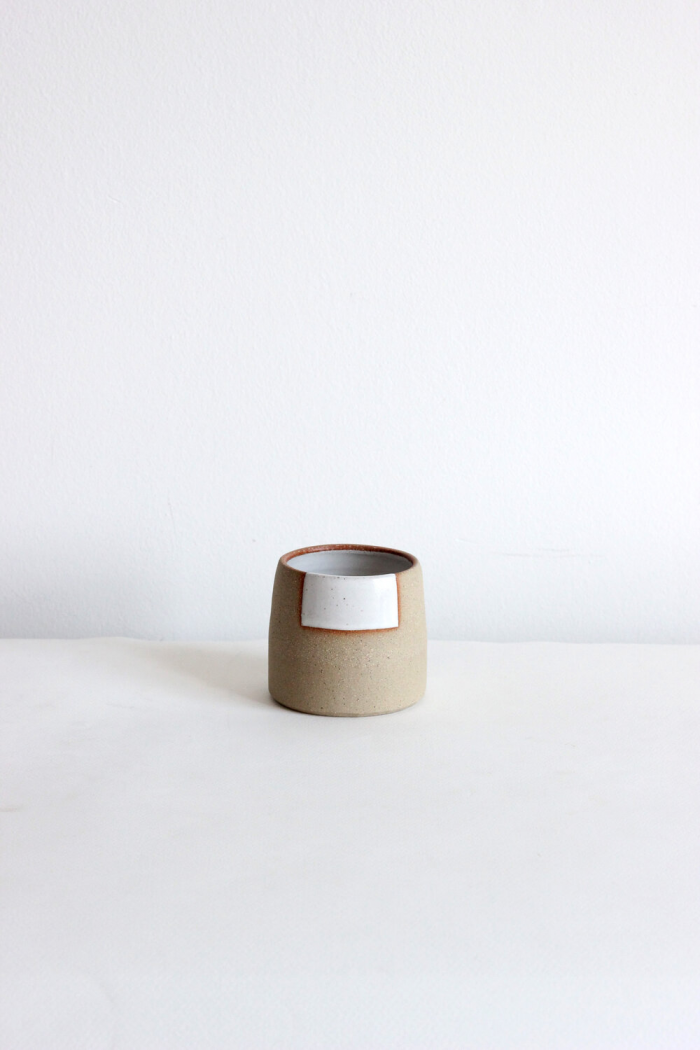 Small, simple coffee cup in a light brown, no handle with a rough geometric pattern of a white square on the rim with a red trim.