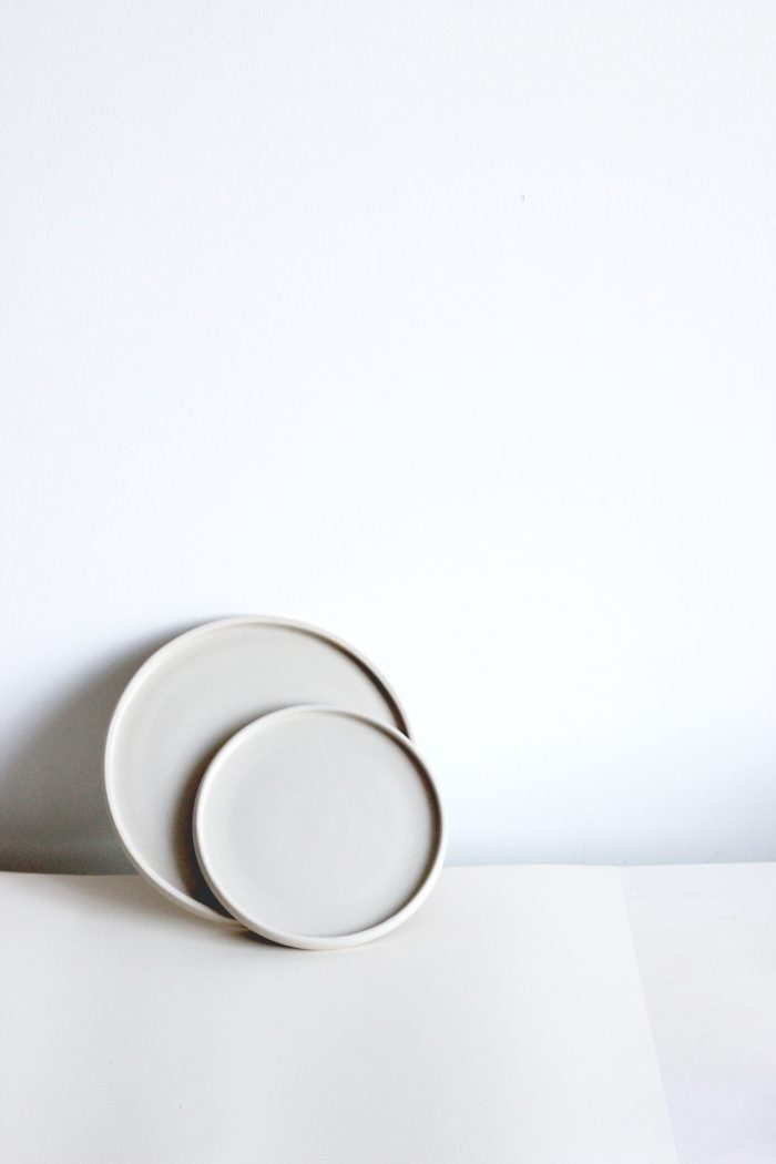 Simply elegant dinner plate with a white base and a small brown rim.