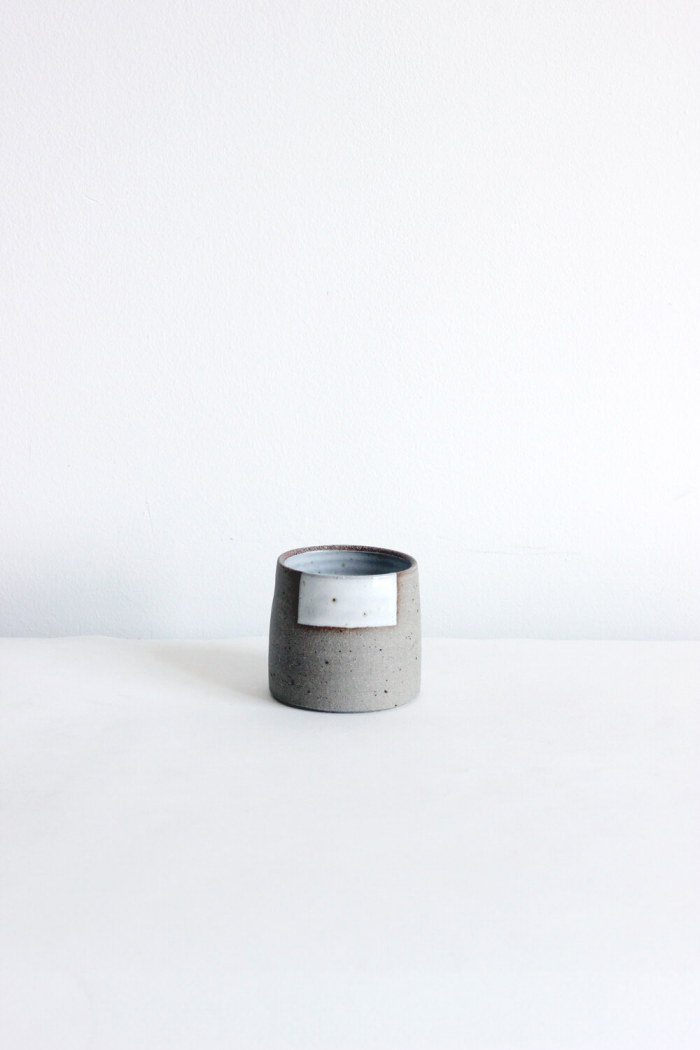 Muted grey stone coffee cup with a simple shape, no handle. It has a geometric rough white square design at it's rim.