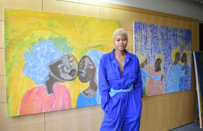 Artist Sola Olulode in a bright blue jumpsuit standing confidently, hands in pockets. Behind them are two colourful, large canvases on a wall.