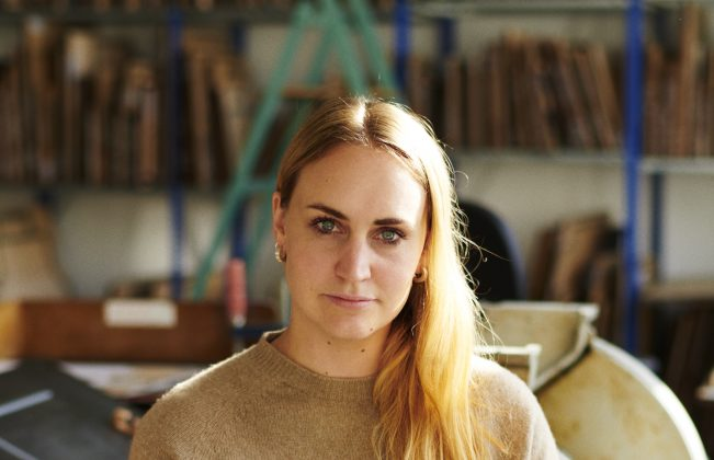 Artist Sophie Rowley sits in her studio in a camel sweater and jeans and looks confidently at the camera.