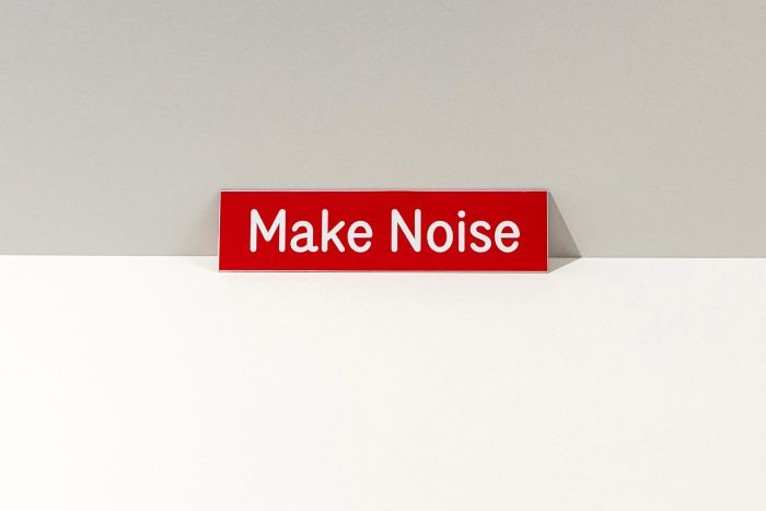 Small red sign that says Make Noise in white.