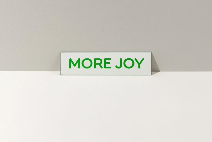 Small, white sign that says More Joy in green letters.