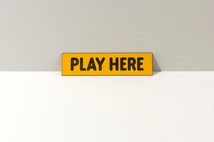 Small yellow sign that says Play Here in bold black letters.