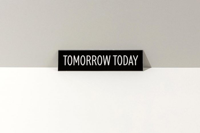 Small, black sign that says Tomorrow Today in white letters.